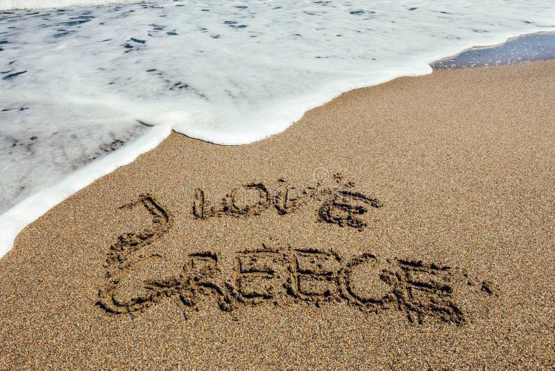 Ordet älskar jag Grekland som är skriftlig i sanden royaltyfri fotografi