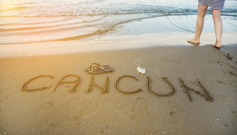 Ordet Cancun som är skriftlig i sanden på stranden härligt barn för kvinna för begreppspölsemester royaltyfri bild