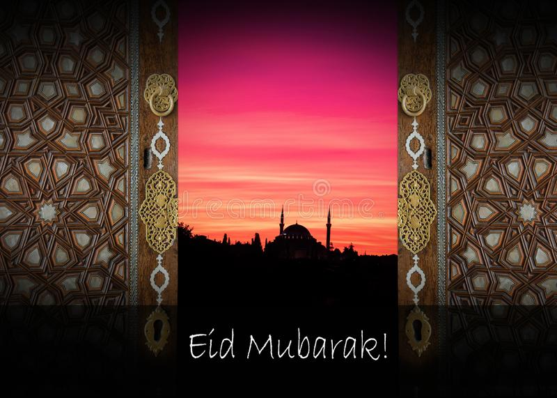 ordet EID MUBARAK som är skriftlig bredvid en moské royaltyfri foto