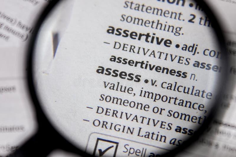 Ordet eller uttrycket bedömer i en ordbok arkivbild