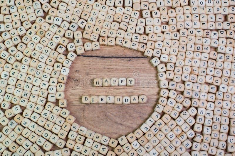 Ordet för den lyckliga födelsedagen i bokstäver på kuben tärnar på tabellen royaltyfria bilder