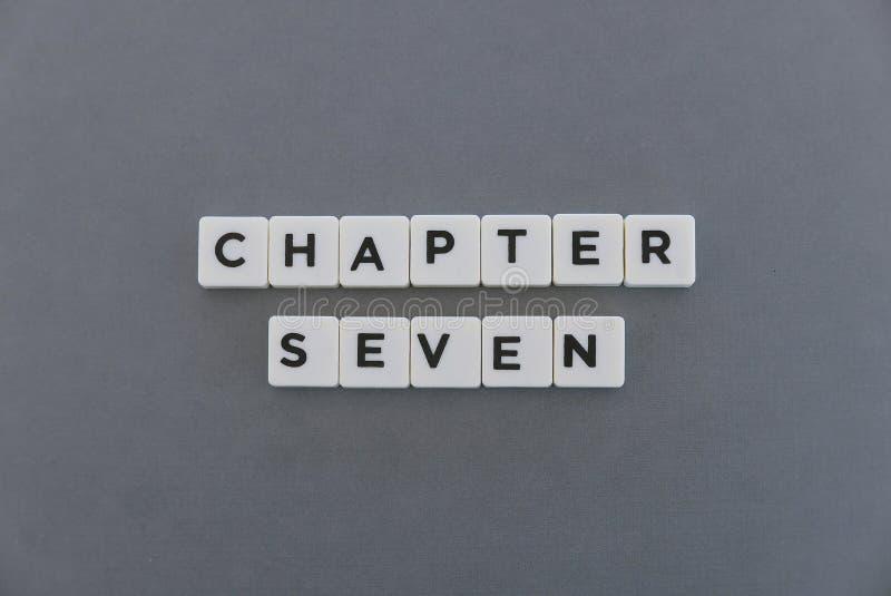 Ordet för kapitel sju gjorde av fyrkantigt bokstavsord på grå bakgrund arkivfoton