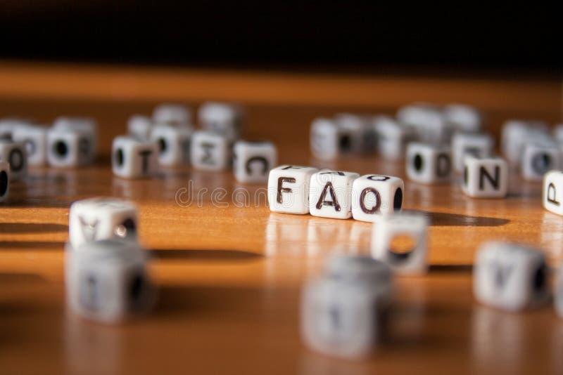 Ordet FAQ som göras av vita plast- kvarter på tabellen fotografering för bildbyråer