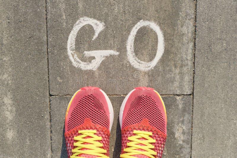 Ordet går skriftligt på den gråa trottoaren med kvinnaben i gymnastikskor, bästa sikt arkivbild