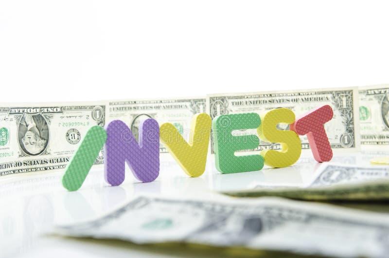 Ordet investerar på mitten av dollarräkningar royaltyfri bild