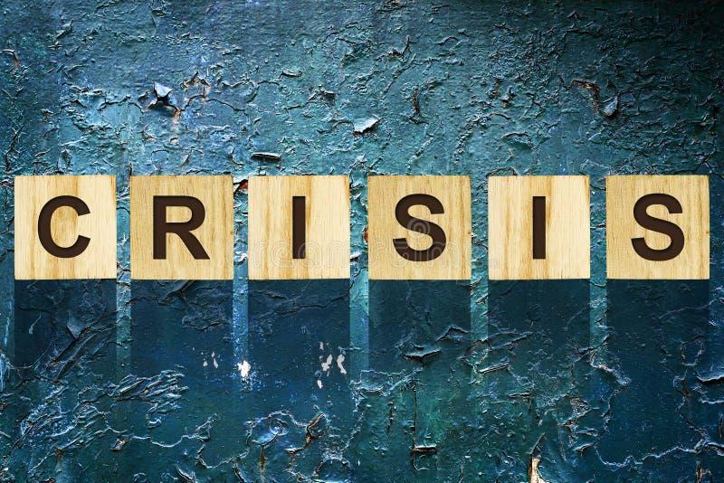 Ordet krisen som komponerades av bokstäver på träkonstruktionskuber mot bakgrunden av gammalt kulört, knäckte järn Begreppsaffär royaltyfri foto