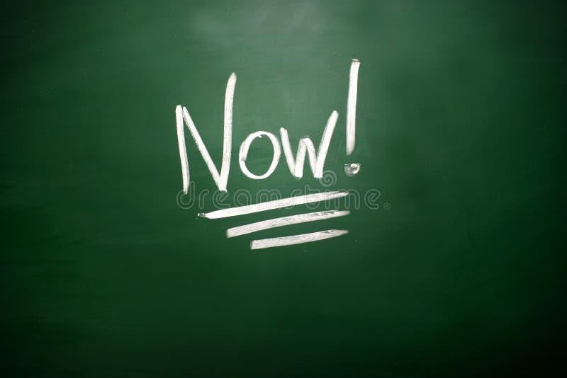 Ordet nu! på svart tavla Ett begrepp för tidledning royaltyfri fotografi