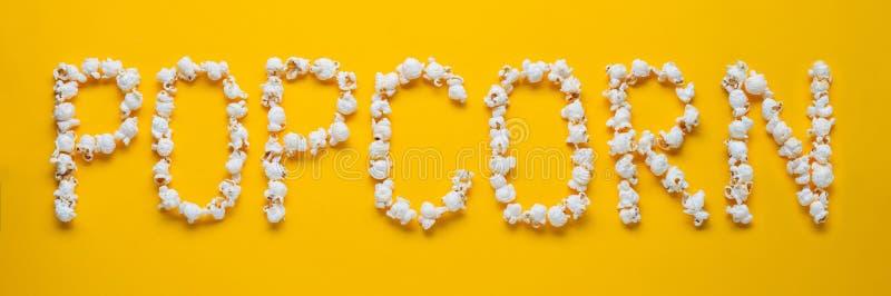 Ordet POPKORN läggas ut från stycken av saltar popcorn på en gul bakgrund Top beskådar Lekmanna- lägenhet royaltyfri fotografi