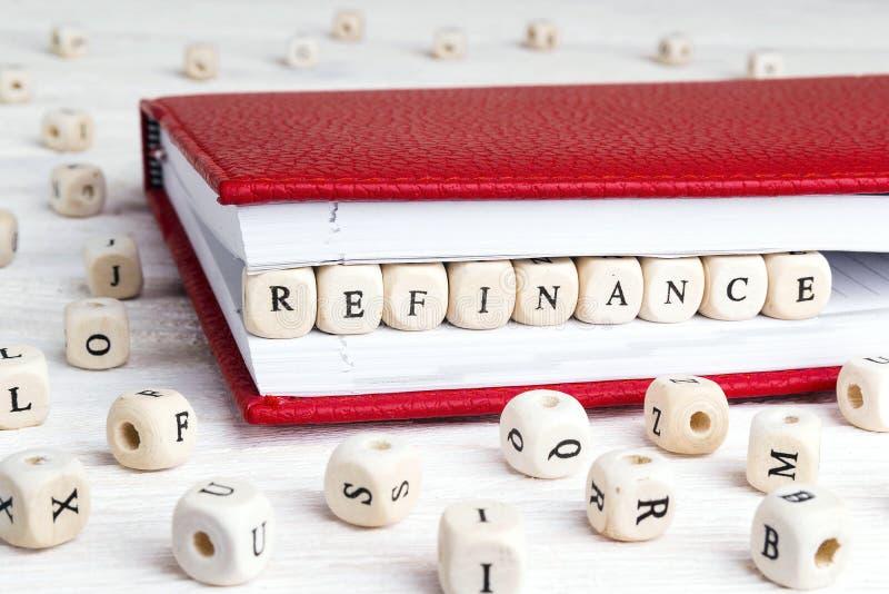 Ordet Refinance skriftligt i träkvarter i röd anteckningsbok på den vita trätabellen royaltyfri bild