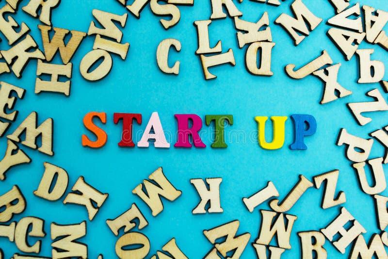 Ordet 'startar 'läggas upp ut från mångfärgade bokstäver på en blå bakgrund royaltyfria bilder