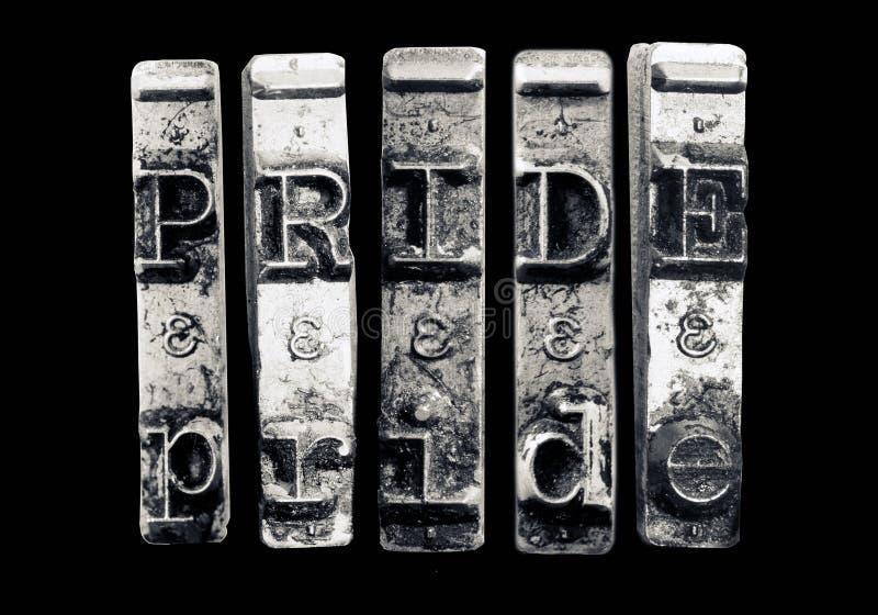 Ordet STOLTHET med gamla skrivmaskinshammare arkivbilder