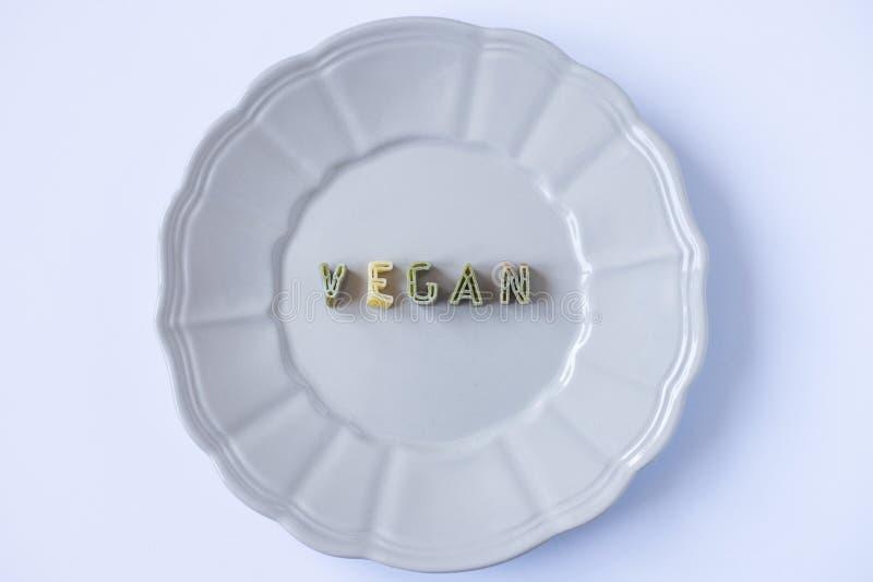 Ordet 'strikt vegetarian 'som är skriftlig med pastabokstäver i en rosa maträtt arkivbilder