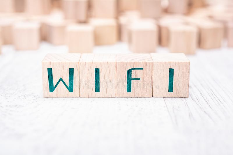 Ordet WIFI som bildas av träkvarter på en vit tabell royaltyfri bild