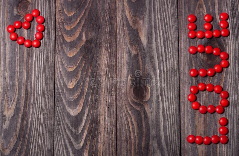Ordförälskelse från godisen på träbakgrund inbunden vektor för valentin för daghjärtaillustration s två arkivbild