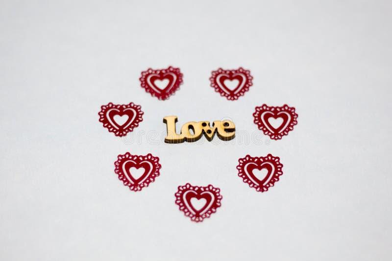 Ordförälskelse i en miljö av röda hjärtor Träinskrift Openwork plast- för hjärtor royaltyfria foton
