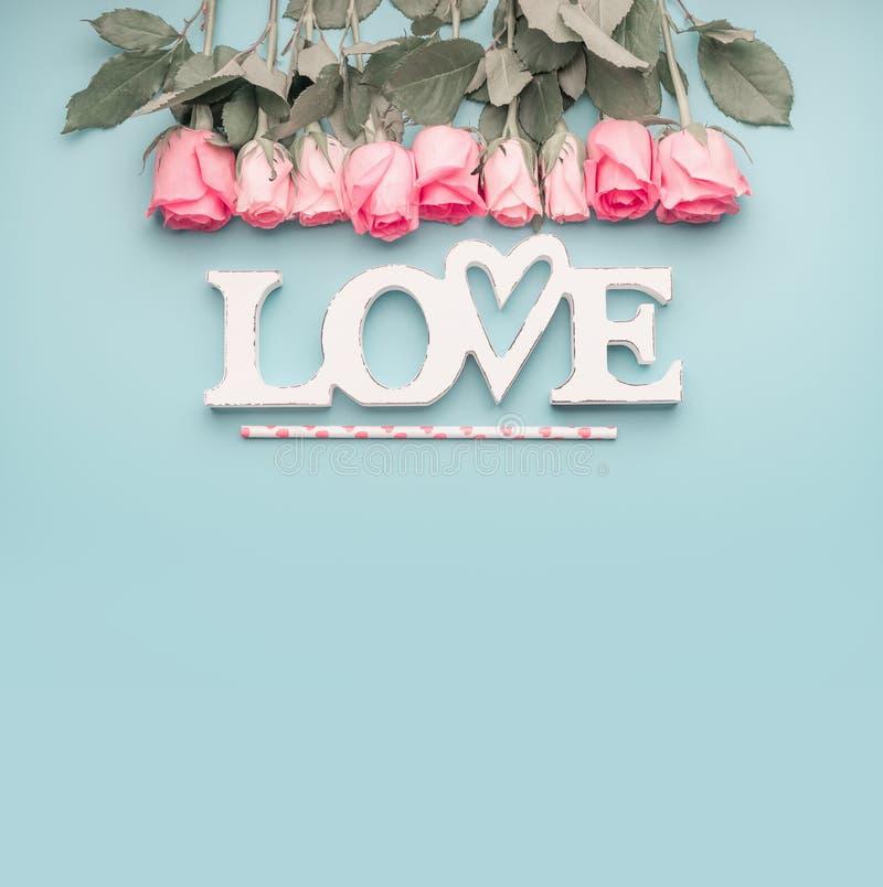 Ordförälskelse med rosor gränsar på pastellfärgad blå bakgrund, bästa sikt med kopieringsutrymme Valentindag eller abstrakt föräl arkivfoto