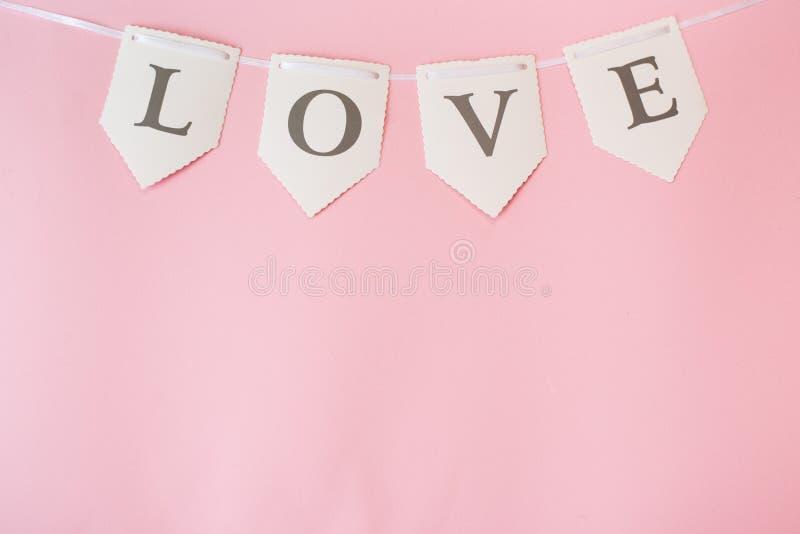 Ordförälskelse på pastellfärgad rosa bakgrund, bästa sikt med kopieringsutrymme Valentindag eller abstrakt förälskelse som gifta  royaltyfri bild
