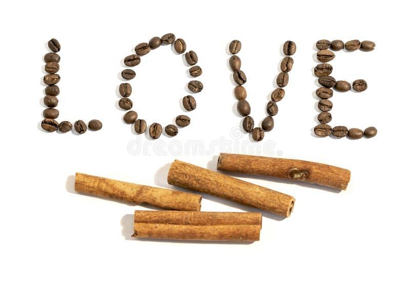 Ordförälskelsen som är skriftlig med den kanelbruna pinnen och kaffebönor på whi royaltyfri bild