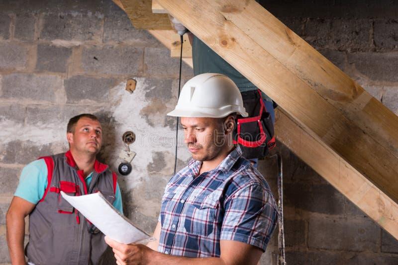Ordförande med plan som övervakar arbete på trappuppgång arkivfoto
