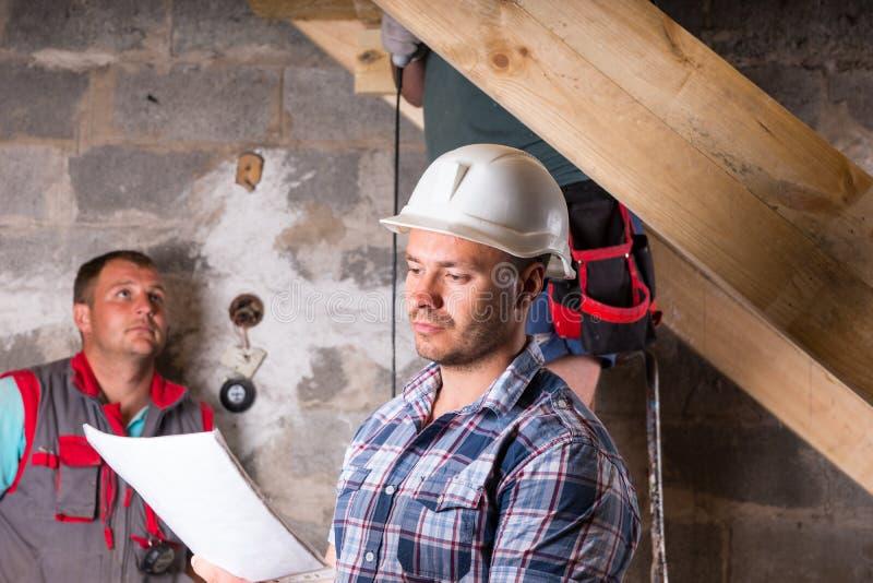 Ordförande med plan som övervakar arbete på trappuppgång fotografering för bildbyråer