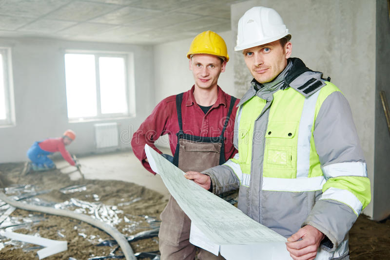 Ordförandebyggmästare och byggnadsarbetare med ritningen i inomhus lägenhet royaltyfri fotografi
