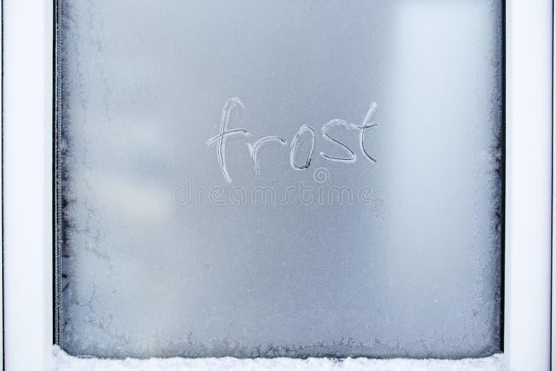 Ordfrosten är skriftlig på ett djupfryst pvc-fönster med härliga modeller och snö royaltyfri bild