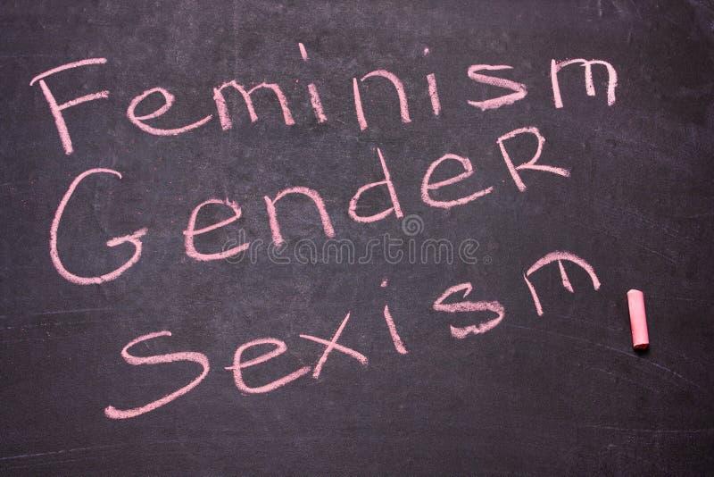Ordgenuset, feminism, könsdiskriminering är skriftlig krita royaltyfri bild