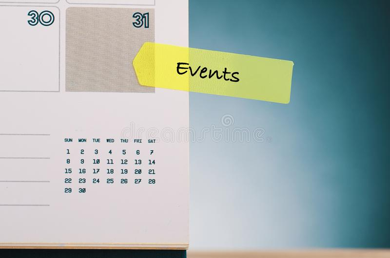 OrdHÄNDELSER som är skriftliga på gult klibbigt papper och kalender över härlig genljudandelutningbakgrund royaltyfri foto
