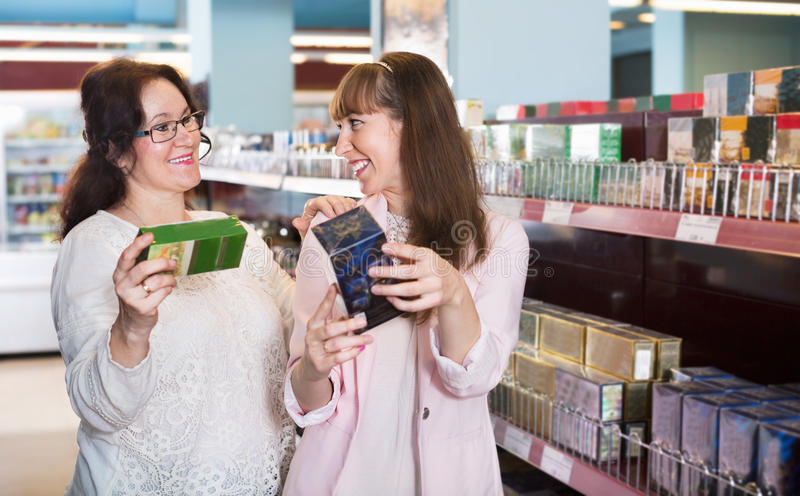 Ordinary cheerful women looking at boxes of tea stock photo