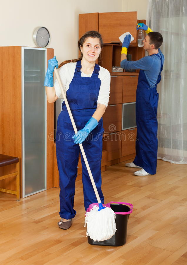 Ordinary cleaners cleaning living room royalty free stock photography