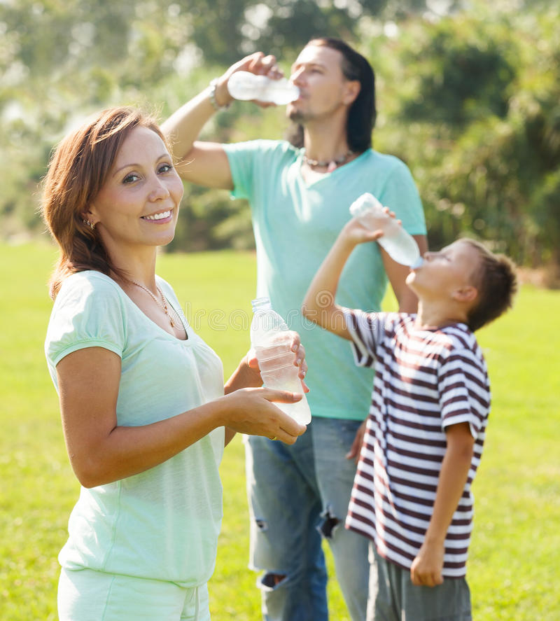 Ordinary couple with teenager drinking water royalty free stock images