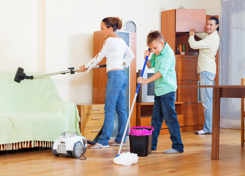 Ordinary family of three with teenager doing housework. With cleaning equipment in living room stock photography