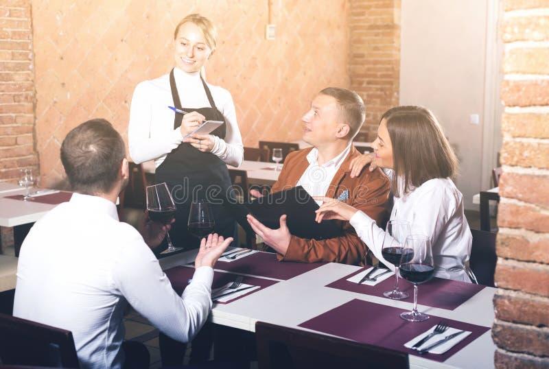 Ordinary female waiter writing down order stock photos