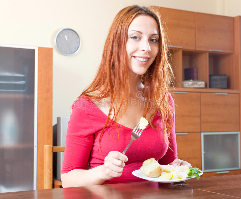 Ordinary girl eating potatoes at home stock photography