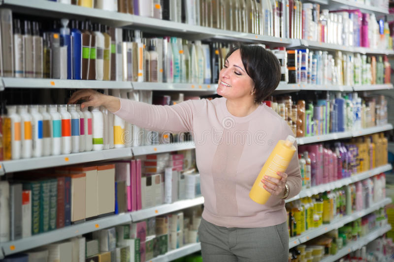 Ordinary Happy female customer choosing conditioner for hair. In beauty store royalty free stock photos