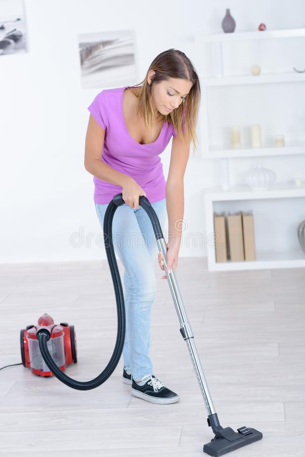 Ordinary housewife in casual dress hoovering surfaces stock image