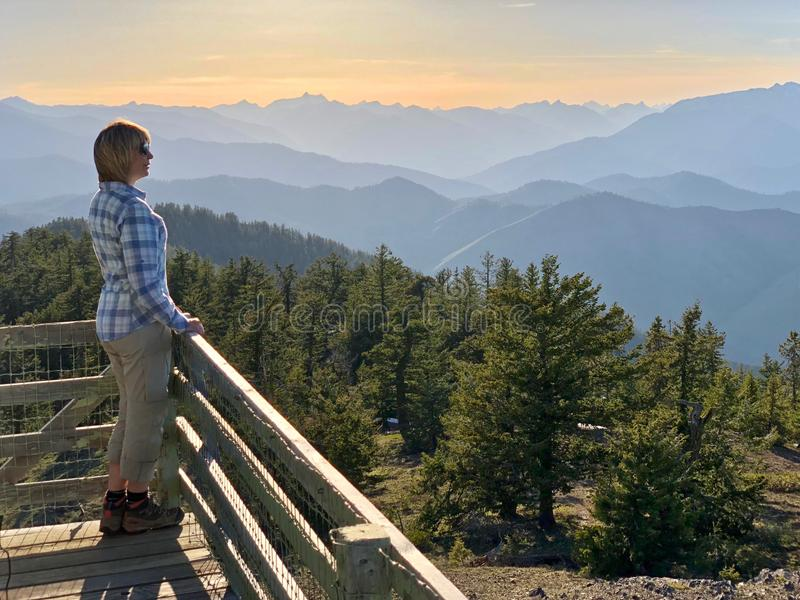 Ordinary middle age woman hiker on the balcony of fire watch tower enjoying beautiful views of mountains at sunset. stock image