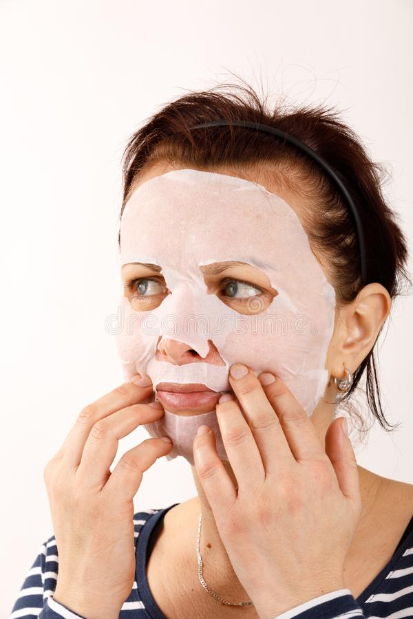 Housewife woman with a sheet mask on her face royalty free stock photo