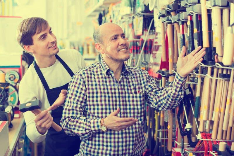 Ordinary positive smiling customer and seller choosing hammer royalty free stock photos