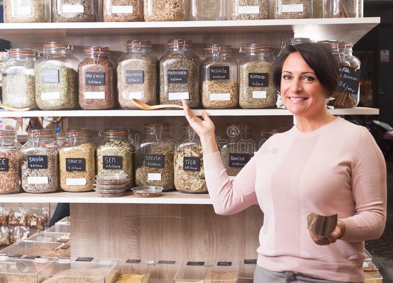 Woman buyer selects herbs in store of ecological products. Ordinary woman buyer selects herbs in store of ecological products royalty free stock photos