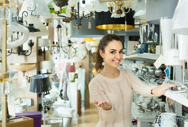 Ordinary woman doing shopping in lighting shop. Ordinary young russian woman doing shopping in lighting shop stock photography