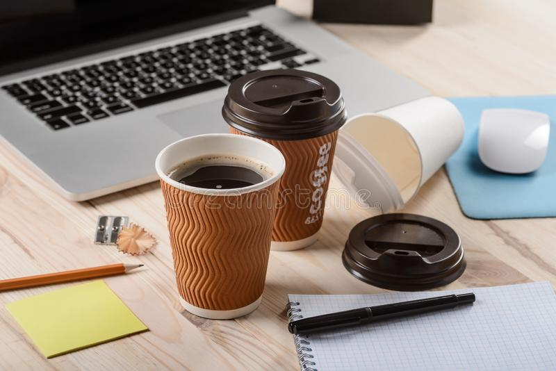 An ordinary working place of a work dork. With three cups of coffee to finish the task. Pencil, pen, sticky notes and laptop on the wooden desk royalty free stock photo