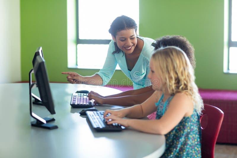 Ordinateur de enseignement de professeur féminin avec des enfants photographie stock