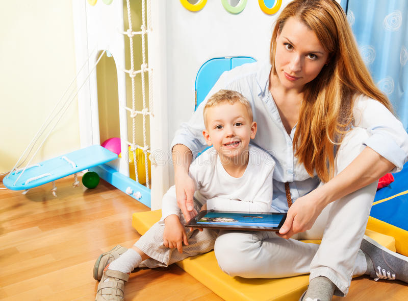 Ordinateur de maman, de fils et de tablette images stock