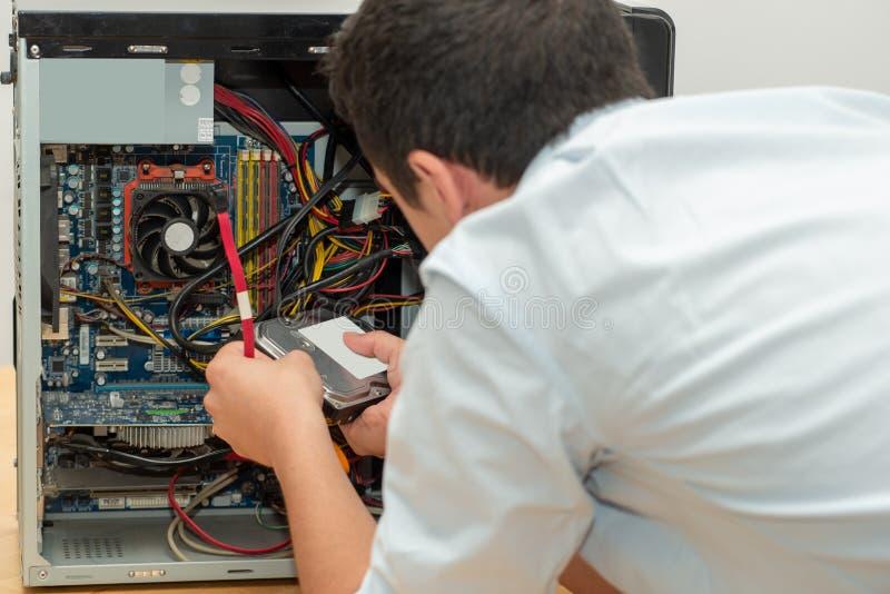 Ordinateur de réparation de technicien de jeune homme photographie stock