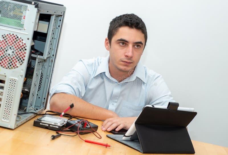 Ordinateur de réparation de technicien de jeune homme photographie stock libre de droits