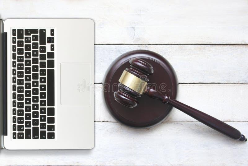 Ordinateur portable à côté d'un marteau de juge sur un bureau en bois blanc Du concept ci-dessus de crime de cyber et de l'espace photos libres de droits