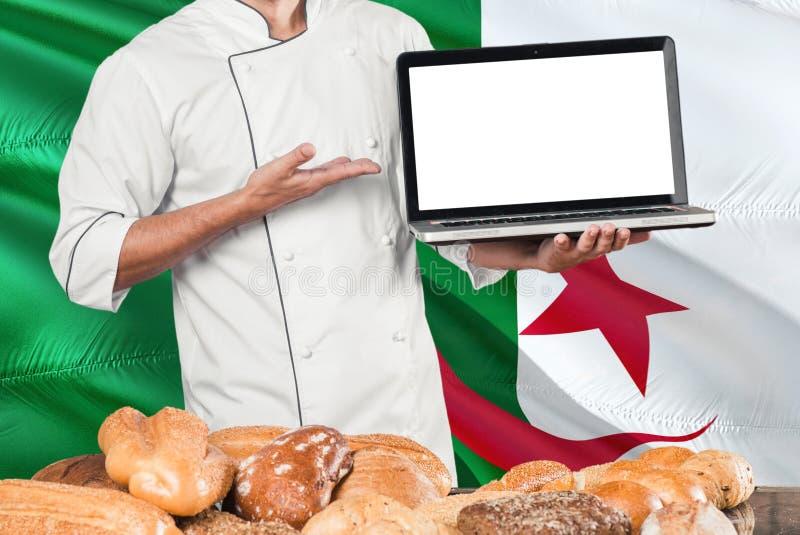 Ordinateur portable algérien de participation de Baker sur le drapeau de l'Algérie et le fond de pains Uniforme de port de chef d images stock