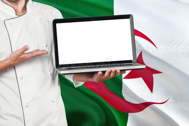 Ordinateur portable algérien de participation de chef avec l'écran vide sur le fond de drapeau de l'Algérie Faites cuire l'unifor images stock