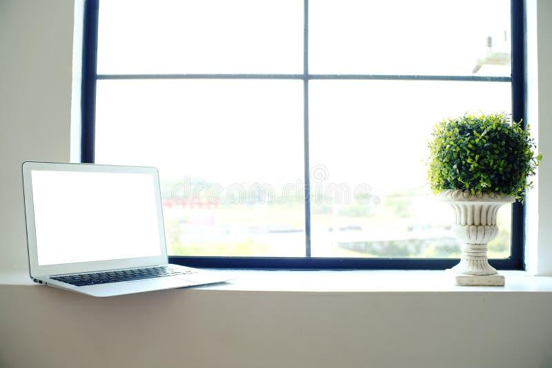 Ordinateur portable avec l'écran vide sur la table en bois devant la fenêtre photographie stock